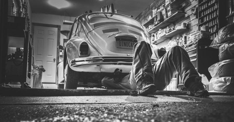 man-repairing-his-car-in-garage-vw-beetle